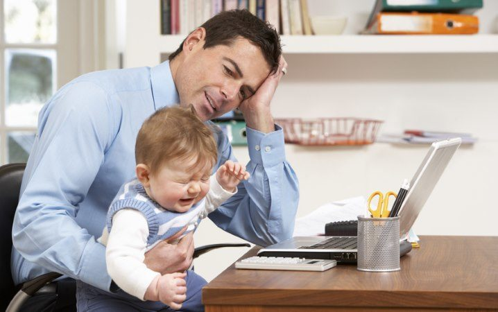 Gestresster Familienvater mit Kind auf dem Schoß: MANNdat thematisiert die Doppelbelastung aus Arbeit und Familie.