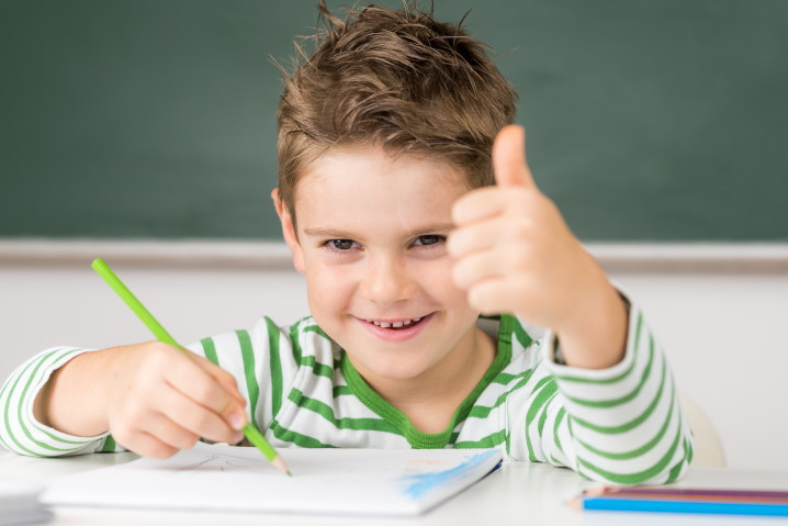 Junge in Schule zeigt Daumen hoch